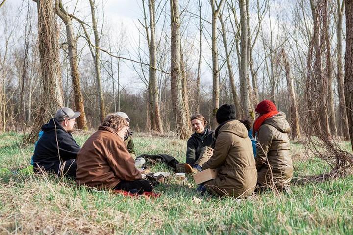 Der Kreis von Teilnehmern versammelt sich nach einer Übung zur Reflexion im Wald