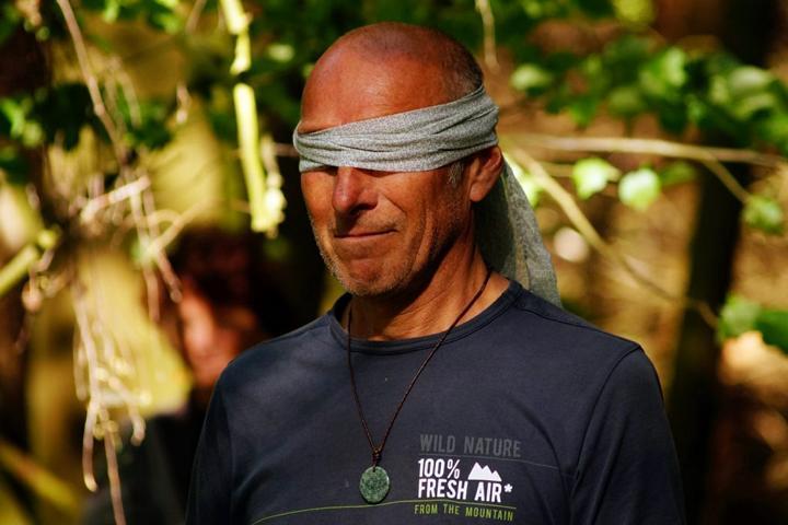 Ein Mann mit verbundenen Augen im Wald bei einer Sinnesübung