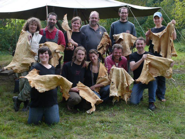 freudige Teilnehmer eines Gerbkurses zeigen ihre fertigen Leder